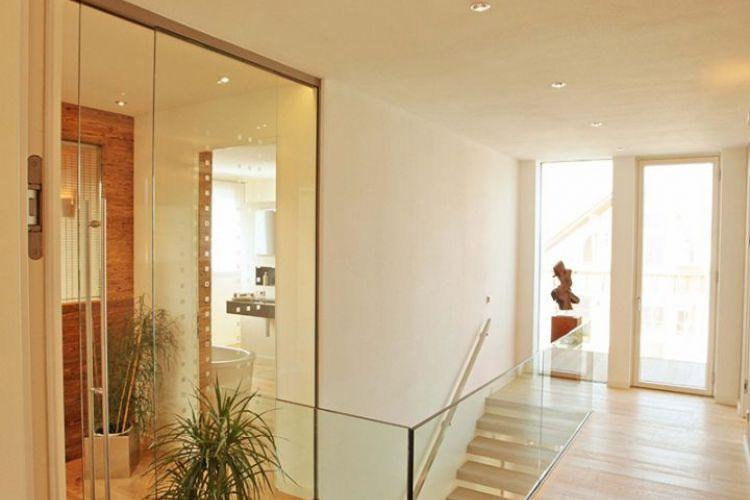 Moderner, heller Flur. Offene Raumgestaltung mit Parkettboden. Musterhaus in München