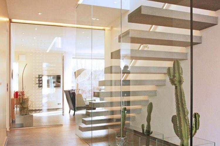 Moderner Treppenaufgang im Rötzer Musterhaus in München. Lichtdurchflutete Räume durch moderne Innengestaltung mit Glas und Fenstern. Offene Raumgestaltung.