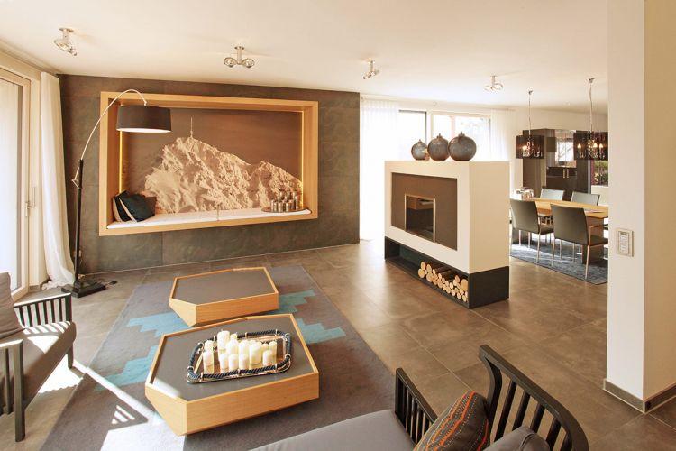 Modernes, helles Wohnzimmer im Musterhaus in München. Freistehender Kamin. Moderne Innenraumgestaltung.