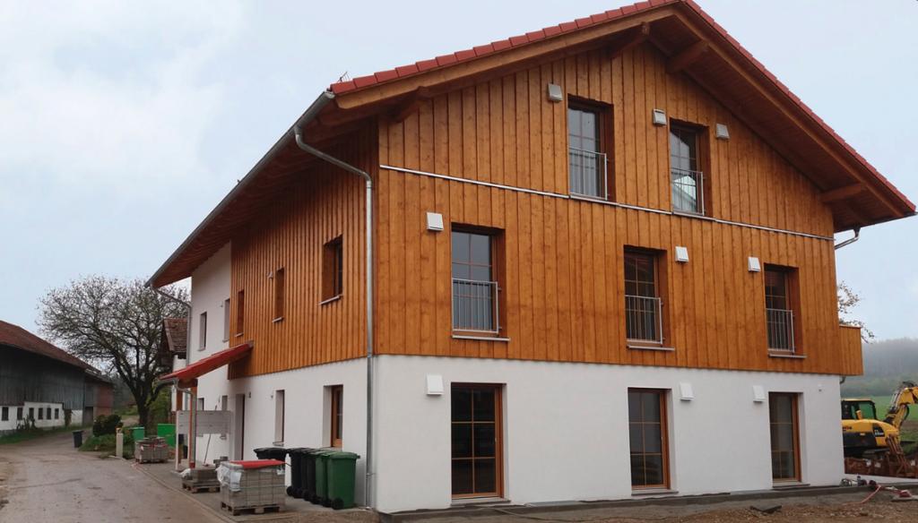 Mehrfamilienhaus mit verschiedenen Hausfassaden-Arten (Holz & Putz)