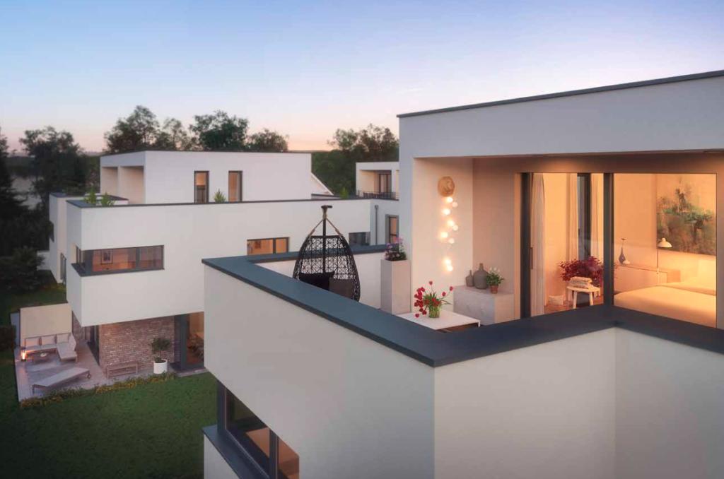 Zu sehen ist der Balkon einer der Rötzer Doppelhaushalten am Ammersee mit Sicht auf das Nachbarhaus. Die Innenräume sind beleuchtet. Der Himmel ist blau, es ist Abenddämmerung.