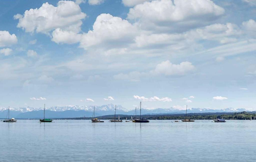 Blick auf den Ammersee. Einzelne Segelboote sind zu sehen. Der Himmel ist blau mit einzelnen Wolken