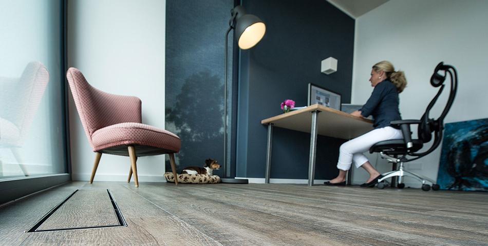 Zentrale Lüftungsanlage von Pluggit mit Designblende im Raum