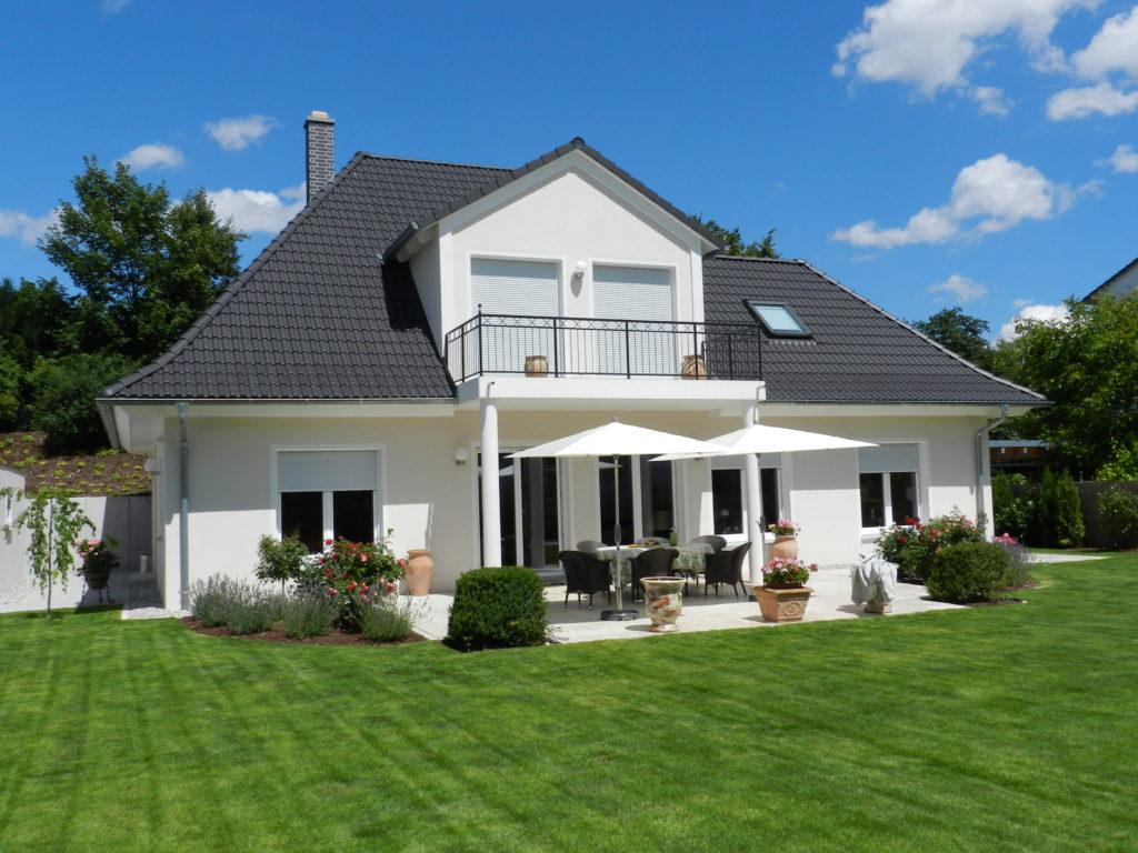 Eine Villa mit Balkon, der zum Garten hinaus geht und somit gleichzeitig die Terrasse überdacht.