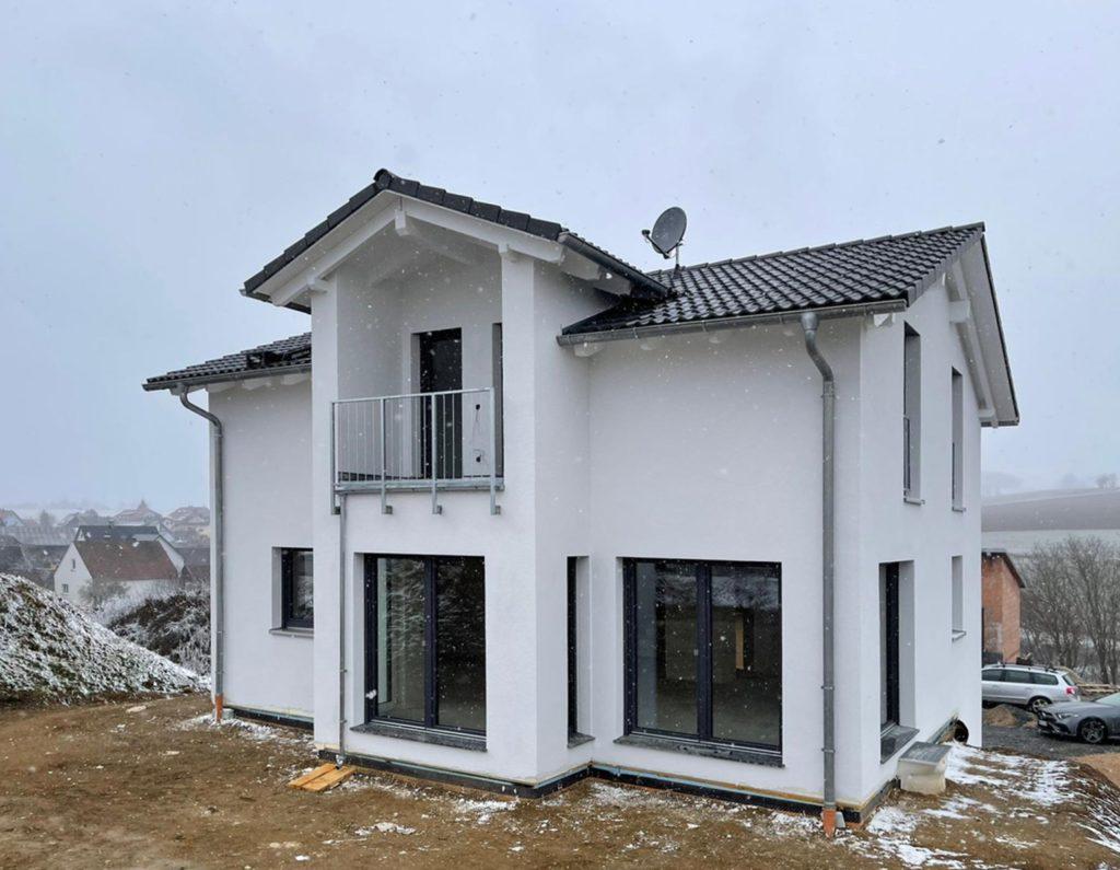 Bei diesem Einfamilienhaus wurde der Balkon in das herausstehende Zwerchhaus integriert.