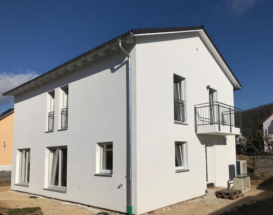 Einfamilienhaus mit Satteldach und freischwebendem Balkon.